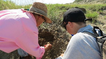 Marge Baisch teaches digging techniques to a young paleontologist.