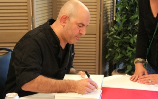 "Simon Majumdar of Cutthroat Kitchen signing his book, ""Fed, White, and Blue."""