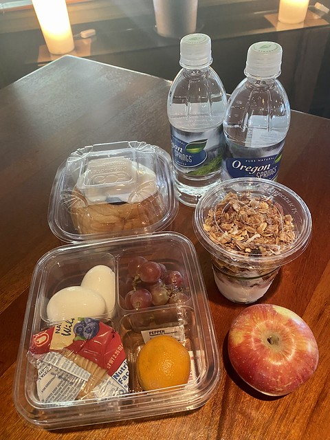 Best Western Hood River Grab n Go breakfast includes yogurt with granola, muffin, fruit, hard boiled eggs and bottled water or a cinnamon roll packaged in plastic containers.