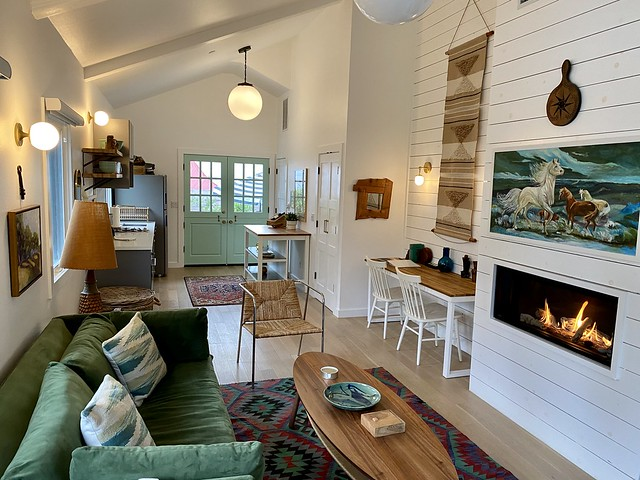 Interior of Bungalows of Calistoga with high white ceilings, gas fireplace, galley kitchen & small living room in Calistoga, California.
