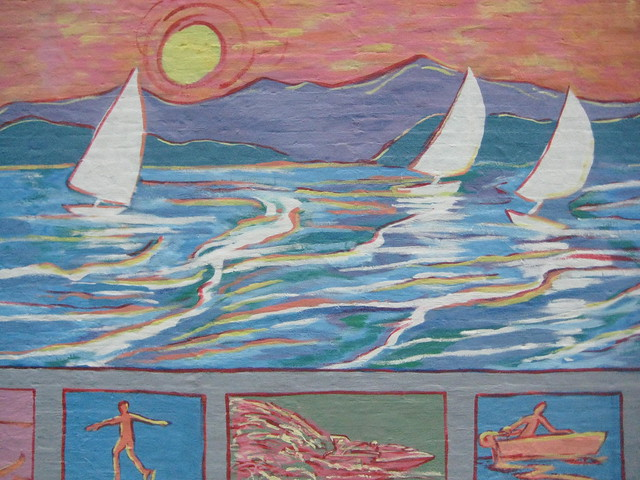 Street art mural in downtown Coeur d'Alene, Idaho shows a watercolor scene of three sailboats on the water with a sun setting into the lake.