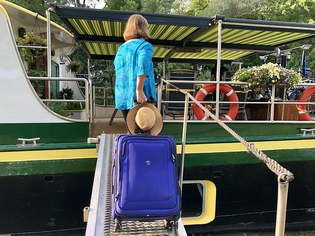 Travel writer Nancy D. Brown boards a barge cruise in Alsace, France with her Delsey suitcase on the gangway.