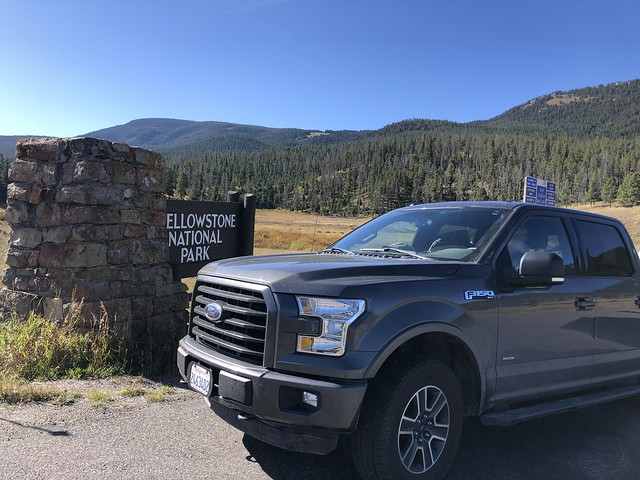 Ford F150 gray truck is parked in front of the sign to Yellowstone National Park, southeast of Big Sky.