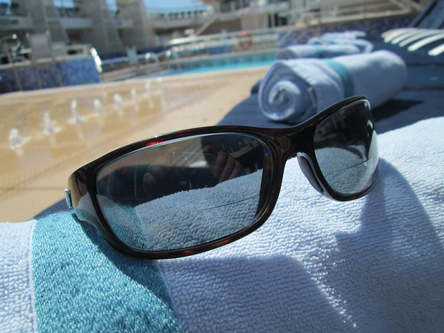 Guideline prescription sunglasses rest on a beach towel on a cruise ship swimming pool deck docked in San Francisco.