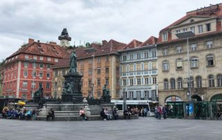 Hauptplatz historical town square surrounded by medieval buildings, foundtain and shops