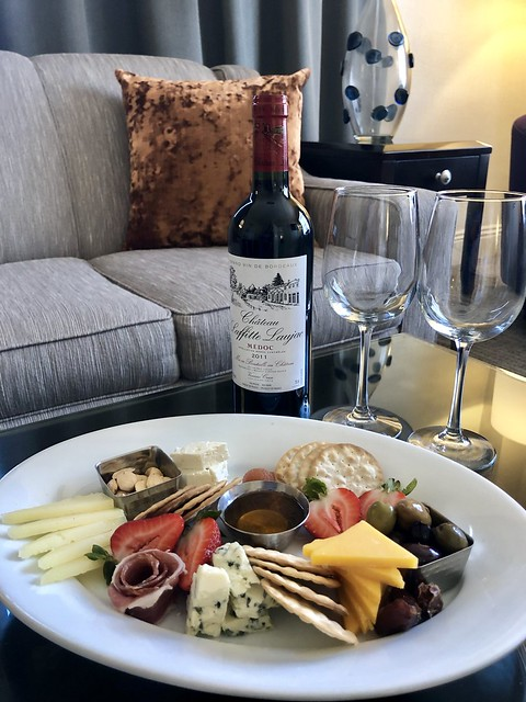 Cheese, crackers, strawberries, olives, nuts and honey are served on a plate, along with a French bottle of red wine at Hotel Shattuck Plaza.