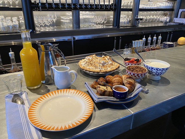 Bistro breakfast at Hotel Cerro, including orange juice, pastry basket, granola, fruit and yogurt.