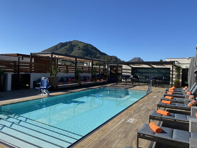 Hotel Cerro rooftop pool Cerro San Luis mountain in the background. Lounge chairs and folded orange towels await hotel guests in downtown San Luis Obispo. with Cero