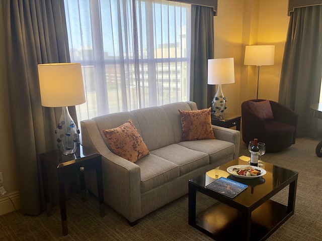 San Francisco Bay view with sofa, coffee table, cheese plate, bottle of French wine & wine glasses await hotel guests.