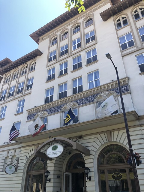 Flags of the United States, California and UC Berkeley hang from the front entrance of Hotel Shattuck Plaza.