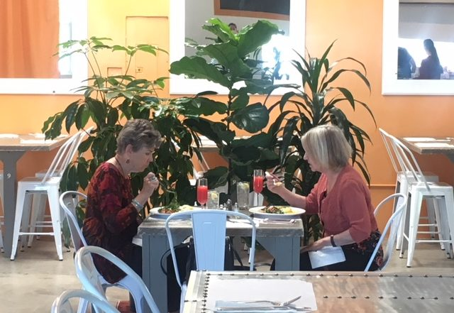 two women eating and drinking at restaurant table