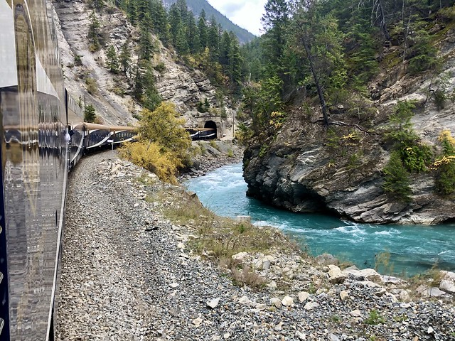 Rocky Mountaineer luxury train heads into a tunnel with the glacial blue water of the Kicking Horse river on the ride side of the train in British Columbia, Canada.