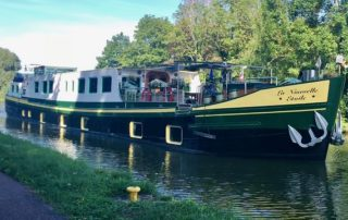 129 feet long and 17 feet wide, the luxury hotel barge, La Nouvelle Etoile, glides along Marne Rhone Canal in Alsace, France. The green and yellow luxury barge is adorned with flower boxes and has a hot tub on board.