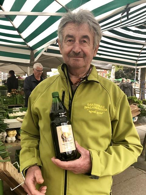 Gartenbau Langbauer farmer holding bottle of pumpkin seed oil at farmers market on Lendplatz.