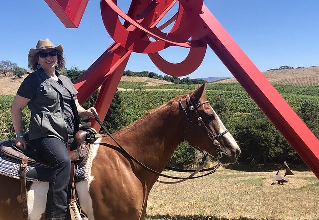"Equestrian travel writer Nancy D. Brown rides her horse through the di Rosa Center for Contemporary Art in Napa, California. She is in front of Mark di Suvero's sculpture entitled ""For Veronica"" di Rosa."