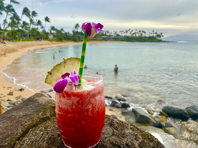 Napili Kai Lava Flow cocktail with Napili Bay in the background, Maui, Hawaii.