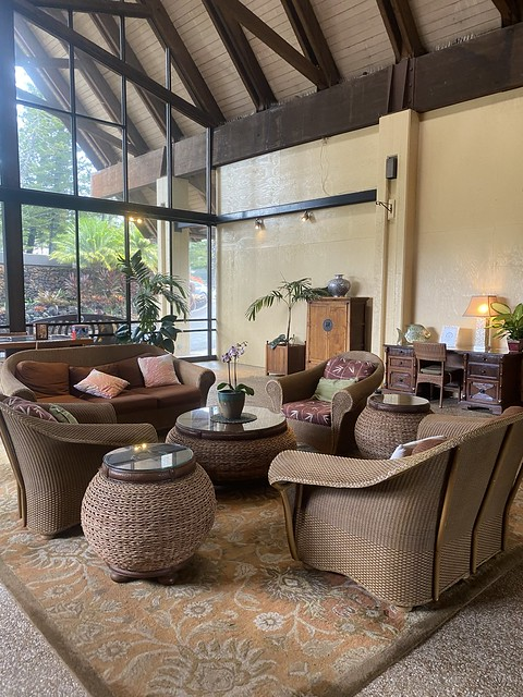 Rattan furniture, tropical orchids invite guests into the open air lobby at Napili Kai Beach Resort in Maui, Hawaii.