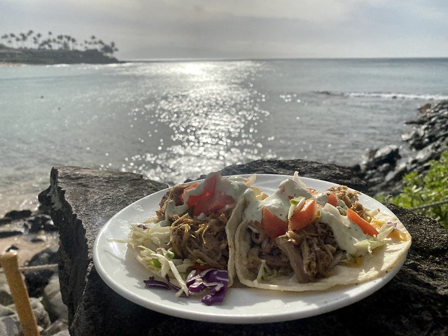 Pork Tacos on a plate with Napili Kai Beach in the background, Maui, Hawaii.