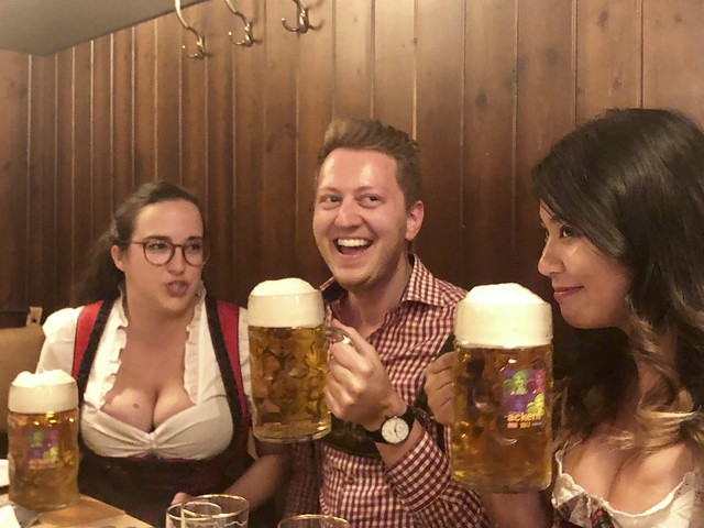 travel bloggers Penelope Bielckus, Patrick Muntzinger and Christina Guan, dress in traditional costume and drink Austrian beer