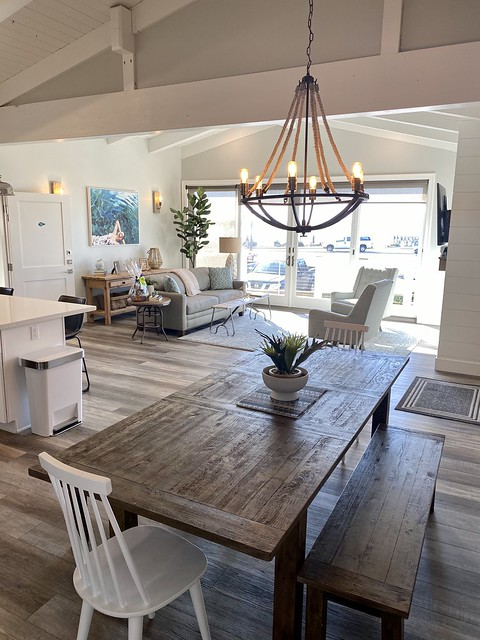 Rustic wood dining room table, bench seats, nautical chandelier over table, opens to living room at Salty Sister Hotel.
