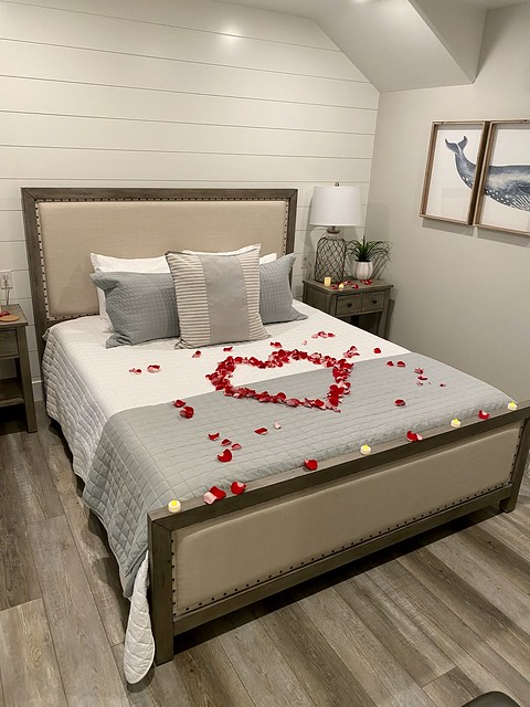 Rose petals, shaped in a heart, are arranged on the bedspread in Spinnaker suite at Salty Sister Hotel.