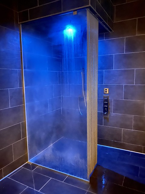 Blue chromatherapy light showers down from the plumbing fixture at Spa Cerro.