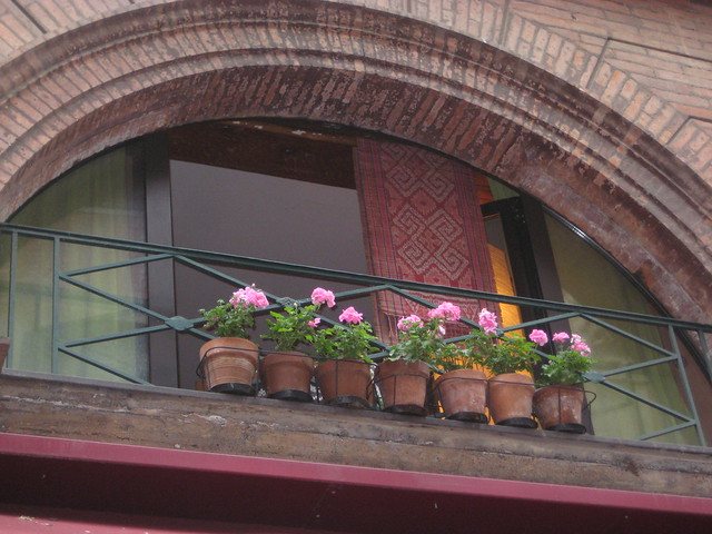 Pink bricks and potted Geraniums line the windows along Rue Tolosane, one of the things to see in Toulouse, France.