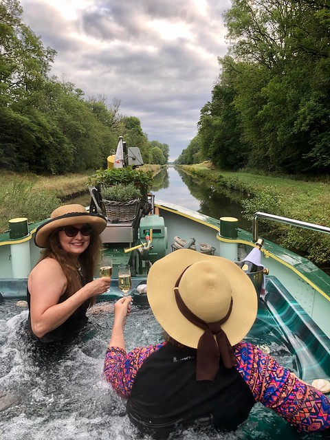Ava Roxanne Stritt and Travel Blogger Nancy Brown toast with a glass of champagne in the hot tub while floating down Canal de la Marne au Rhine in a hot tub on board a barge in Alsace, France.