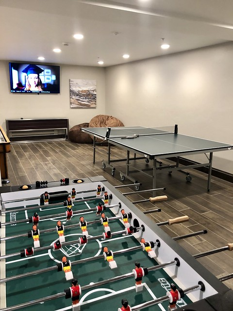 Hotel game room includes tv, fossball, ping pong table and shuffleboard.