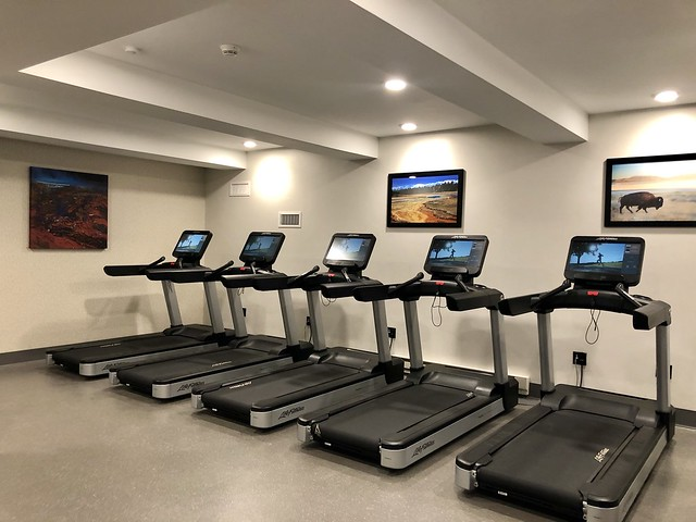 Hotel fitness center with five cardiovascular treadmills with wireless TV screens..