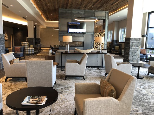Earth-toned chairs, glass lamps and a see-through fireplace decorate the lobby of The Wilson Hotel Residence Inn Big Sky.