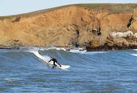 image of surfer with cliffs in background